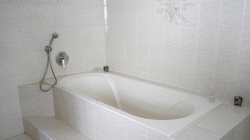 und das Badezimmer mit Dusche und Badewanne.